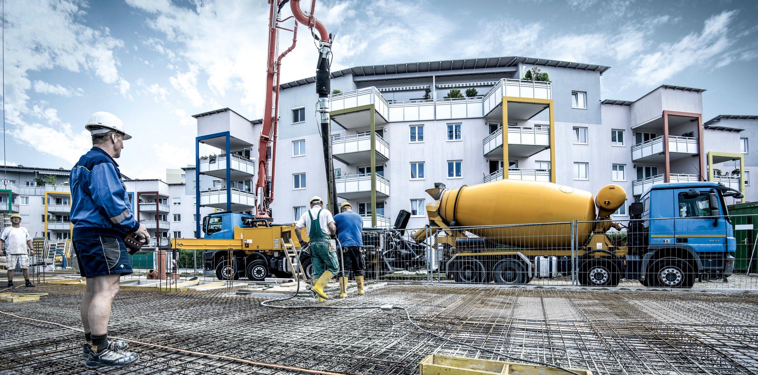 Betonpumpe fördert Transportbeton auf eine Baustelle, auf der eine Fundamentplatte betoniert wird