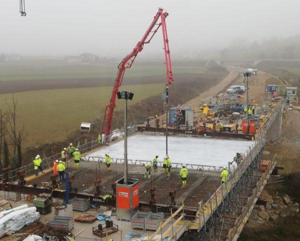 Betonpumpe transportiert Transportbeton auf eine Brückenbaustelle
